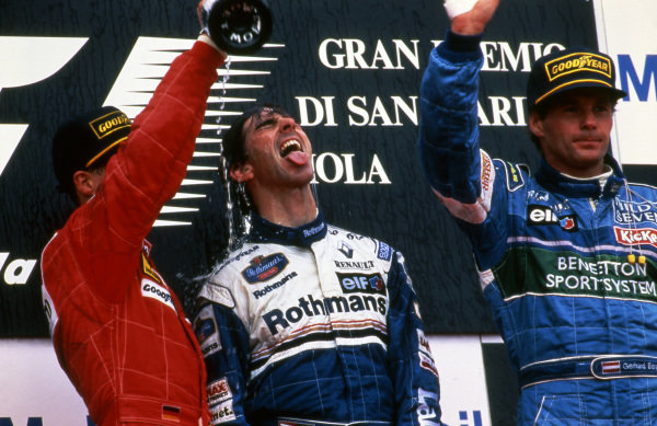 Race winner Damon Hill (GBR) Williams celebrates with the champagne on the podium with second placed Michael Schumacher (GER) Ferrari and Gerhard Berger (AUT) Benetton at Formula One World Championship, San Marino Grand Prix, Rd5, Imola, Italy, 5th May 1996.