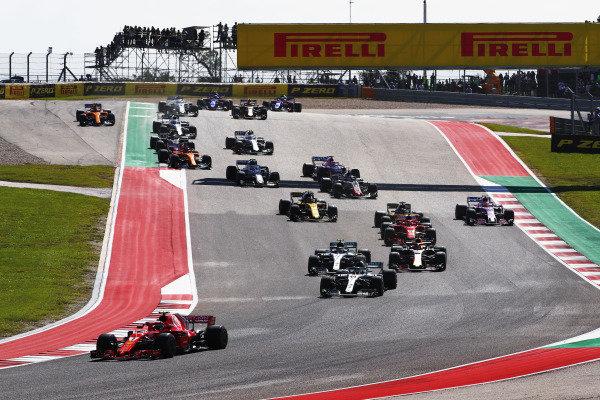 Kimi Raikkonen, Ferrari SF71H, leads Lewis Hamilton, Mercedes AMG F1 W09 EQ Power+, at the start of the race
