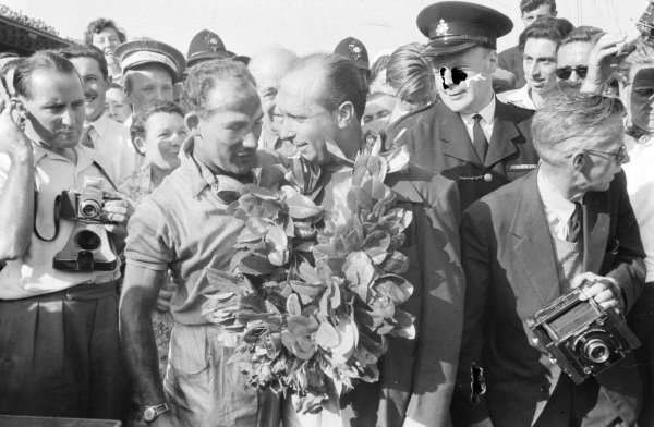 Stirling Moss gives his winner's garland to Juan Manuel Fangio.