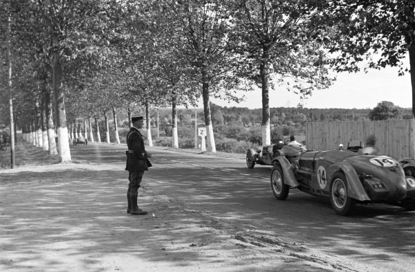 A gendarme watches from the side of the track as Victor Polledry / R. Robert, Aston Martin 1.5, leads Joseph Chotard / Jacques Seylair, Delahaye 135CS.