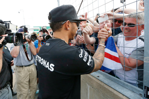Circuit Gilles Villeneuve, Montreal, Canada. Sunday 7 June 2015. Lewis Hamilton, Mercedes AMG, 1st Position, celebrates with and signs autographs for fans. World Copyright: Alastair Staley/LAT Photographic. ref: Digital Image _79P5834