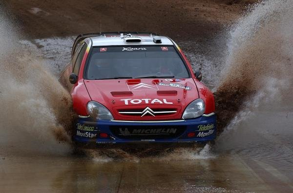 Carlos Sainz (ESP) with co-driver Marc Marti (ESP) Citroen Xsara WRC heads through a mud bath.