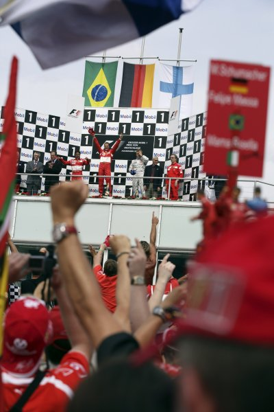 2006 German Grand Prix - Sunday Race Hockenheim, Germany. 27th - 30th July. Michael Schumacher (1st position), and Felipe Massa (2nd position) of Ferrari celebrate on the podium with Kimi Raikkonen (3rd position) of McLaren-Mercedes. Atmosphere, fans. World Copyright: Charles Coates/LAT Photographic ref: Digital Image ZK5Y2450