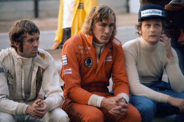 Kyalami, South Africa. 30 March 1974. Ian Scheckter (Lotus 72D-Ford), James Hunt (Hesketh 308-Ford) and Niki Lauda (Ferrari 312B3), sit in the pit lane during a drivers briefing, portrait.  World Copyright: LAT Photographic.  Ref:  74 SA 33.
