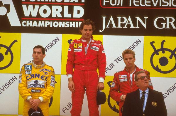 Suzuka, Japan.29/10-1/11 1987.Gerhard Berger (Ferrari) 1st position, Ayrton Senna (Team Lotus) 2nd position and Stefan Johansson (McLaren TAG Porsche) 3rd position on the podium. FIA President Jean-Marie Balestre stands in front.Ref-87 JAP 09.World Copyright - LAT Photographic