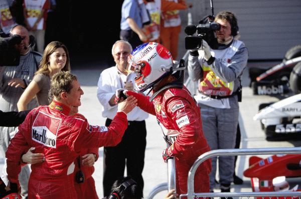 Michael Schumacher congratulates teammate Rubens Barrichello on victory in parc ferme.
