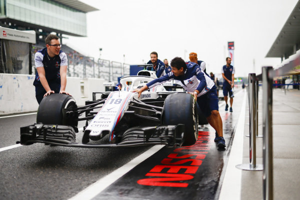 Williams mechanics push the car of Lance Stroll, Williams FW41, in the pit lane.