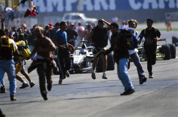Mika Häkkinen, McLaren MP4-15 Mercedes, carefully picks his way through the track invaders after the chequered flag.