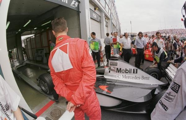 1998 French Grand Prix.Magny-Cours, Nevers, France.26-28 June 1998.Michael Schumacher (Ferrari) takes a close look at the McLaren MP4/13 Mercedes-Benz.World Copyright - Martyn Elford/LAT Photographic