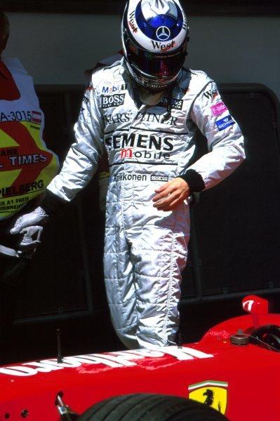 Kimi Raikkonen (FIN) McLaren examines a Ferrari F2002 in parc ferme after qualifying.Austrian Grand Prix, Rd6, A1-Ring, Austria. 13 May 2002.BEST IMAGE