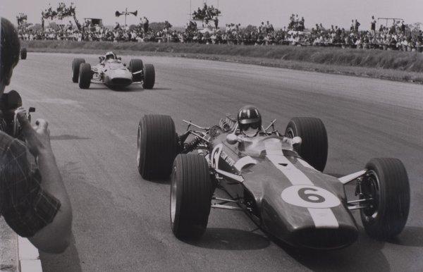 1967 British Grand Prix.Silverstone, Great Britain. 15 July 1967.Graham Hill, Lotus 49-Ford, retired, leads Chris Amon, Ferrari 312, 3rd position, action.World Copyright: LAT PhotographicRef: Motor b&w print