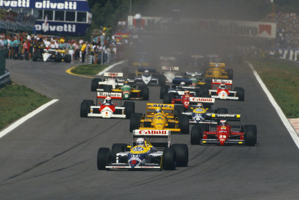 Nigel Mansell, Williams FW11B Honda, leads Gerhard Berger, Ferrari F1-87, Ayrton Senna, Lotus 99T Honda, Nelson Piquet, Williams FW11B Honda, Alain Prost, McLaren MP4-3 TAG, Michele Alboreto, Ferrari F1-87, Riccardo Patrese, Brabham BT56 BMW, Thierry Boutsen, Benetton B187 Ford, Stefan Johansson, McLaren MP4-3 TAG, Eddie Cheever, Arrows A10 Megatron, Teo Fabi, Benetton B187 Ford, Andrea de Cesaris, Brabham BT56 BMW, and Derek Warwick, Arrows A10 Megatron, at the start.