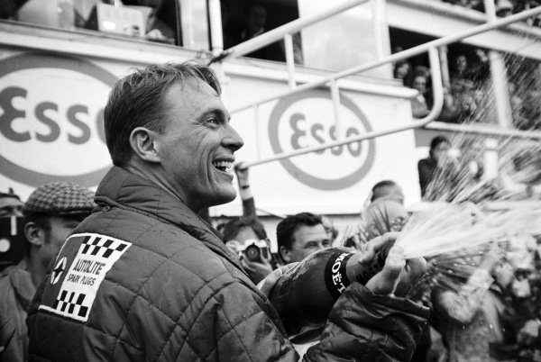 Dan Gurney starts a tradition by spraying his champagne on the podium.