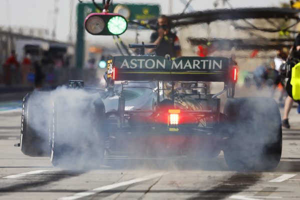 Lance Stroll, Aston Martin AMR21, lights up his rears as he leaves the pits