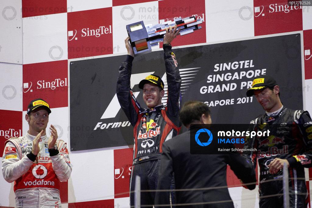 Sebastian Vettel, 1st position, celebrates on the podium with Jenson Button, 2nd position, and Mark Webber, 3rd position.