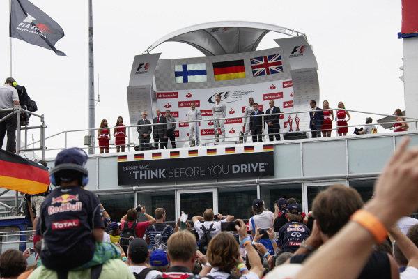 Nico Rosberg, 1st position, Valtteri Bottas, 2nd position, and Lewis Hamilton, 3rd position, on the podium.