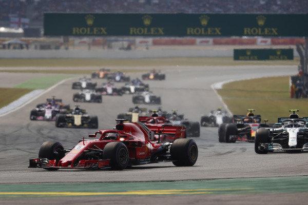 Sebastian Vettel, Ferrari SF71H, leads Valtteri Bottas, Mercedes AMG F1 W09, Kimi Raikkonen, Ferrari SF71H, Max Verstappen, Red Bull Racing RB14 Tag Heuer, and the rest of the pack at the start.