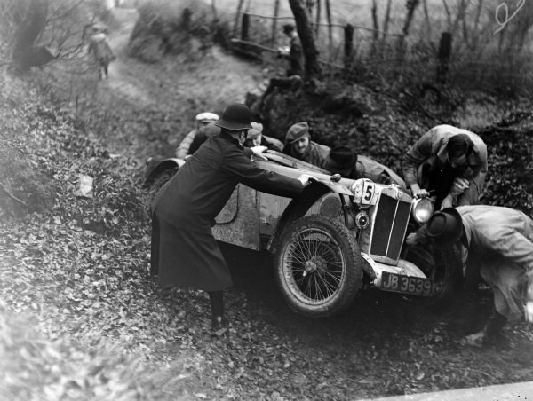 Spectators and a policeman help to free the MG of R. A. Macdermid.