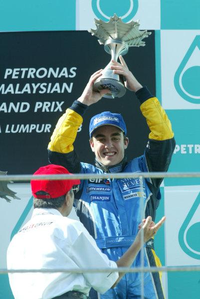 2003 Malaysian Grand Prix. Sepang, Kuala Lumpur, Malaysia.21-23 March 2003.Fernando Alonso (Renault) celebrates his 3rd position on the podium.World Copyright - LAT Photographic ref: Digital Image Only
