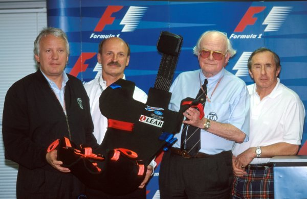 The new 1999 extractable safety seat, designed by LEAR, was on display in Japan with (L to R): Charlie Whiting (GBR) FIA Safety Delegate, a LEAR representative, Doctor Syd Watkins (GBR) FIA Doctor and former World Champion and safety campaigner Jackie Stewart (GBR) Stewart Team Principal.
