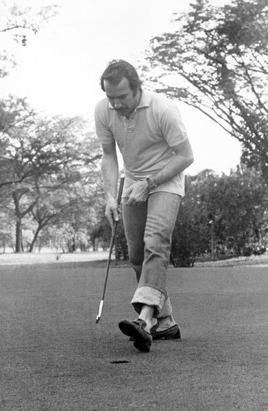 Clay Regazzoni relaxes by playing golf before the race, portrait. 