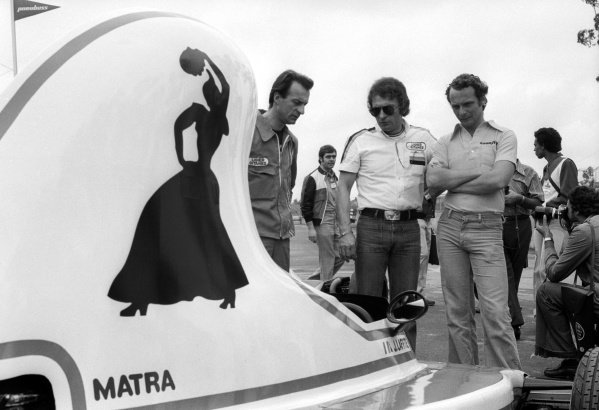 Gerard Ducarouge (FRA) Ligier Team Manager (Centre) shows off his new Ligier JS5, complete with distinctive teapot air box, to race winner Niki Lauda (AUT) Ferrari (Right).Brazilian Grand Prix, Rd1, Interlagos, Brazil, 25 January 1976.