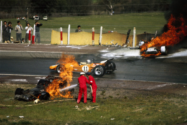 Bruce McLaren, McLaren M14A Ford, drives between the burning BRM P153 of Jackie Oliver and Ferrari 312B of Jacky Ickx as marshals work to extinguish the flames.