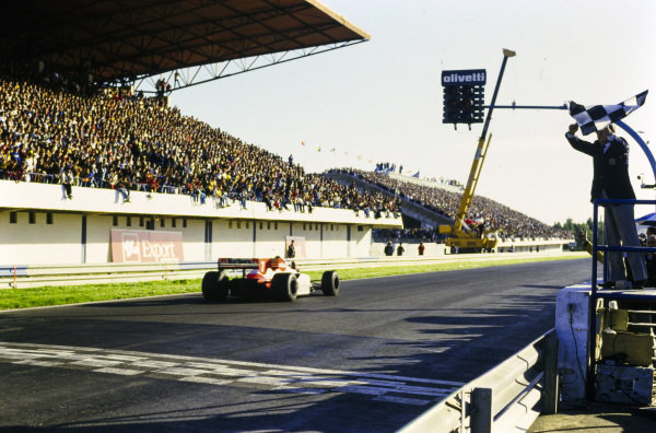 Alain Prost, McLaren MP4-2 TAG, crosses the line and takes the chequered flag, which is waved by Jean-Marie Balestre.
