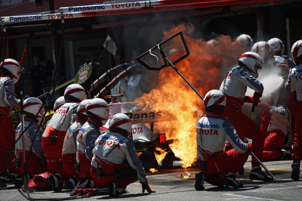 The rear of Jarno Trulli's Toyota TF106 erupts in flame during a pitstop.