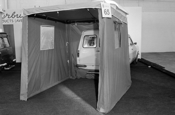 A Ford Escort van based camper with a tent awning.
