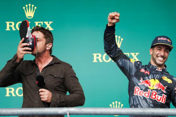 Circuit of the Americas, Austin Texas, USA. Sunday 23 October 2016. Gerard Butler drinks Red Bull from the shoe of Daniel Ricciardo, Red Bull Racing, on the podium. World Copyright: Glenn Dunbar/LAT Photographic ref: Digital Image _31I5379