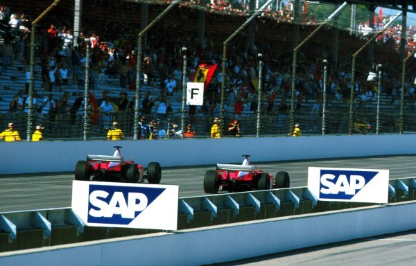 Michael Schumacher (GER), left, and Rubens Barrichello (BRA), right, once again finish controversially. Barrichello, second place throughout the race, unexpectedly won. United States Grand Prix, Rd16, Indianapolis, USA. 29 September 2002. BEST IMAGE
