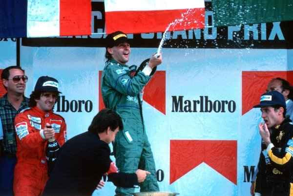 The podium (L to R): Benetton team manager Peter Collins (GBR); second place finisher Alain Prost (FRA); delighted race winner Gerhard Berger (AUT) Ð his first victory and the first for Benetton; Ayrton Senna (BRA) third. Mexican Grand Prix, Mexico City, 12 October 1986.