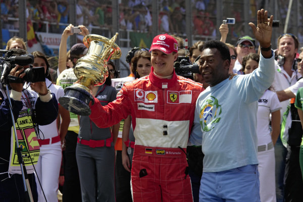 Michael Schumacher with a trophy 'for his remarkable achievements in the world of Formula 1' received from football legend Pelé.