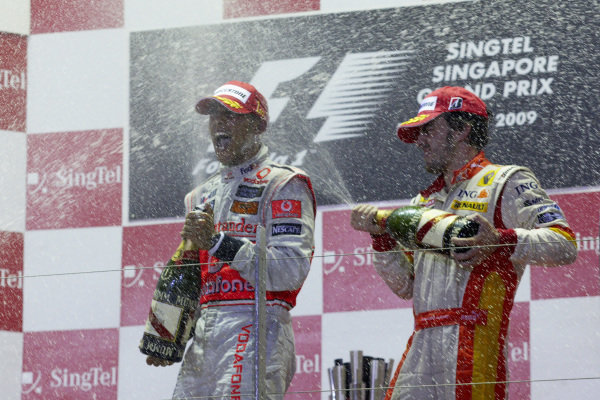 Lewis Hamilton celebrates victory on the podium with Fernando Alonso, 3rd position.