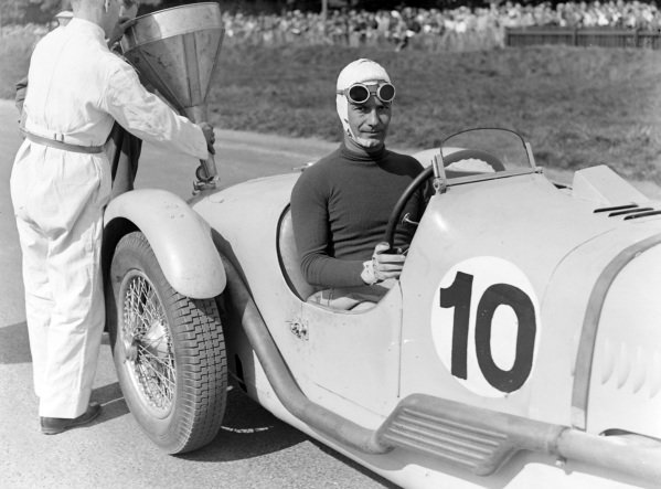 Gianfanco Comotti, Talbot Lago T150C.  In the background mechanics are putting a funnel in to allow for fuel to be put in the car.