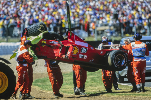 Marshals remove the crashed car of Michael Schumacher, Ferrari F399, from the barrier.