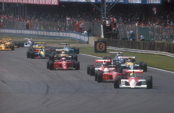 1990 British Grand Prix.Silverstone, England.13-15 July 1990.Ayrton Senna (McLaren MP4/5B Honda) leads Nigel Mansell (Ferrari 641), Gerhard Berger (McLaren MP4/5B Honda), Alain Prost (Ferrari 641), Thierry Boutsen (Williams FW13B Renault), Jean Alesi (Tyrrell 019 Ford), Riccardo Patrese (Williams FW13B Renault) and Aguri Suzuki (Lola 90 Lamborghini) at the start.Ref-90 GB 06.World Copyright - LAT Photographic
