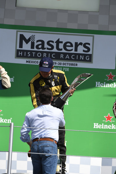 Race winner Katsuaki Kubota ((JPN) ) celebrates on the podium with the trophy at Masters Historics, Circuit Hermanos Rodriguez, Mexico City, Mexico, 29 October 2016.