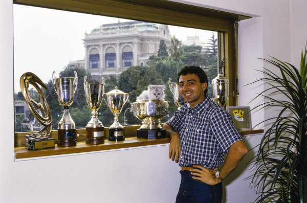 Michele Alboreto, Ferrari, poses next to a line of trophies on a window sill