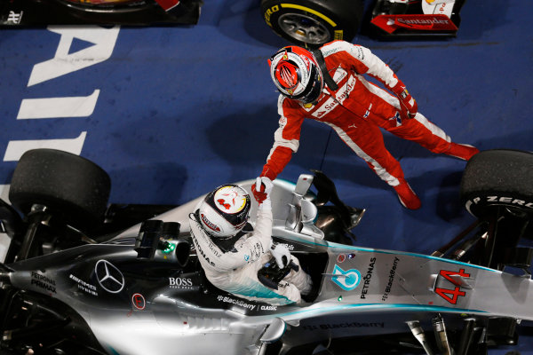 Bahrain International Circuit, Sakhir, Bahrain. Sunday 19 April 2015. Kimi Raikkonen, Ferrari, 2nd Position, congratulates Lewis Hamilton, Mercedes AMG, 1st Position, in Parc Ferme. World Copyright: Steven Tee/LAT Photographic. ref: Digital Image _X0W2360