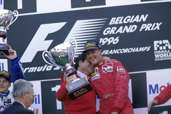 Michael Schumacher celebrates victory with Ferrari team boss Jean Todt on the podium.