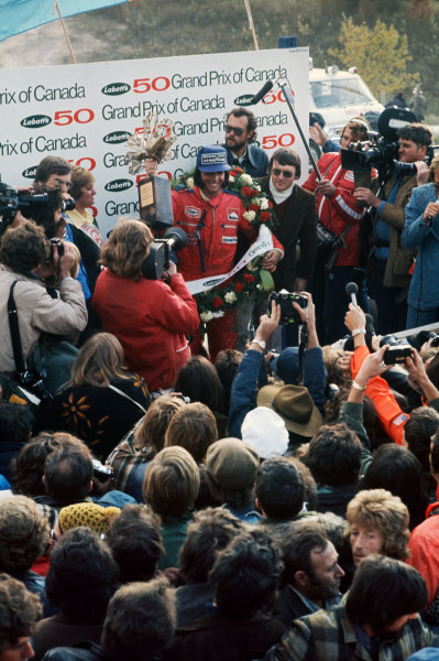 1974 Canadian Grand Prix  Mosport Park, Canada. 22 September 1974.  Emerson Fittipaldi, McLaren M23 Ford, 1st position, celebrates on the podium.  Ref: 74CAN02. World Copyright: LAT Photographic