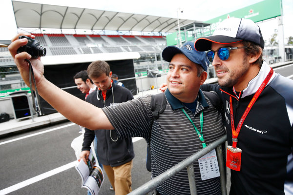 Autodromo Hermanos Rodriguez, Mexico City, Mexico. Thursday 27 October 2016. Fernando Alonso, McLaren, poses for a selfie with a fan. World Copyright: Andy Hone/LAT Photographic ref: Digital Image _ONZ0071