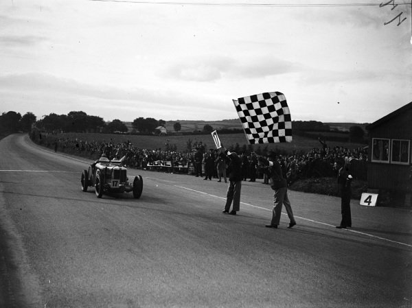 Tazio Nuvolari, MG Magnette K3, crosses the line and takes the chequered flag.