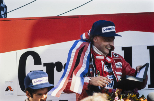 Niki Lauda celebrates victory on the podium.