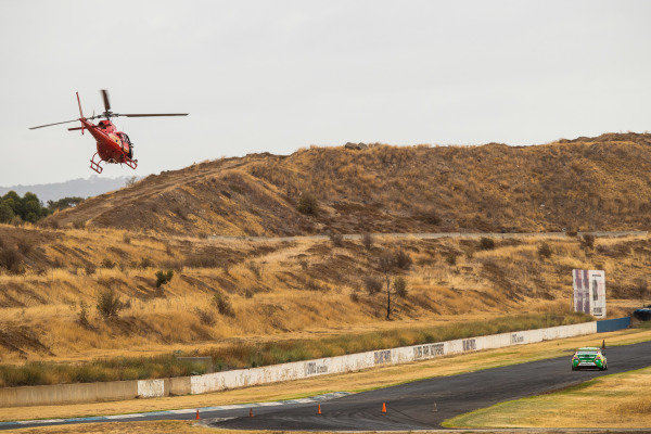 Daniel Ricciardo tests Kelly Racing Nissan Supercar at Calder. A helicopter follows closely