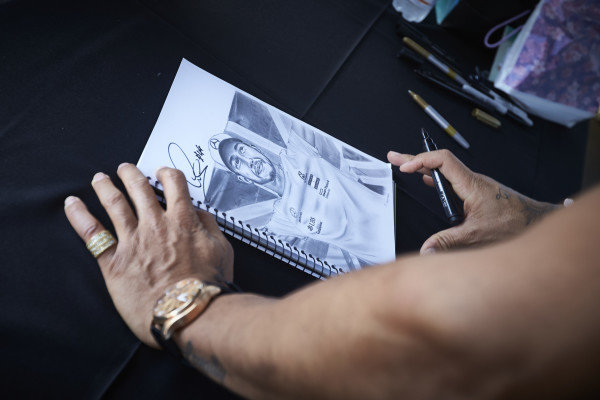 Lewis Hamilton, Mercedes AMG F1 signs autographs for fans on a drawing of himself