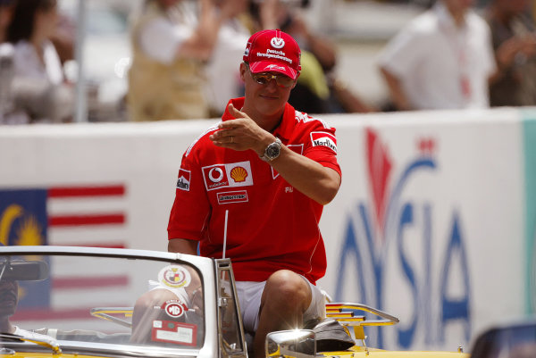 2004 Malaysian Grand Prix - Sunday Race, 2004 Malaysian Grand Prix Sepang, Kuala Lumpur. Malaysia. 21st March 2004 Michael Schumacher, Ferrari F2004 gets a ride round the circuit in an open top sports car in the drivers parade.World Copyright: Steve Etherington/LAT Photographic ref: Digital Image Only