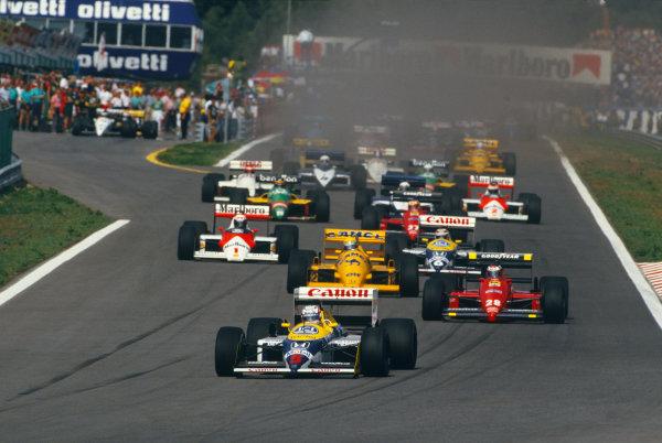 Estoril, Portugal.18-20 September 1987.Nigel Mansell (Williams FW11B Honda) leads Gerhard Berger (Ferrari F187) Ayrton Senna (Lotus 99T Honda), Nelson Piquet (Williams FW11B Honda) and Alain Prost (McLaren MP4/3 TAG Porsche) at the start, action.World Copyright: LAT PhotographicRef:87 POR 09.